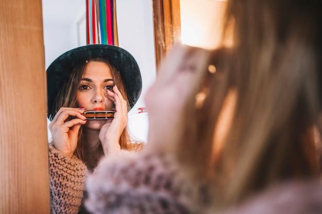 Donna alla moda che suona l'armonica