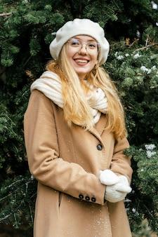 冬の公園でポーズをとるスタイリッシュな女性