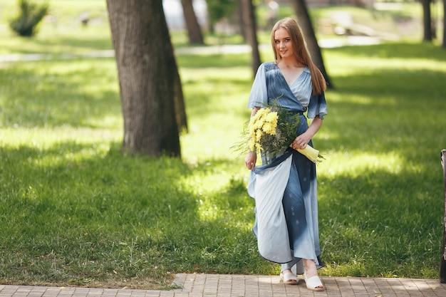 화창한 봄 공원에서 드레스를 입고 포즈를 취하는 세련 된 여자. 봄에 꽃다발로 서있는 아름다운 여자의 진정 초상화