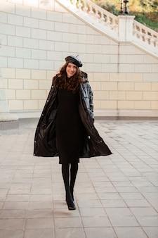 冬の秋のファッショントレンドでポーズをとるスタイリッシュな女性ハイヒールの靴を履いて古い美しい通りで黒のフグコートと革の帽子のベレー帽