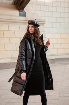 오래 된 아름 다운 거리에서 겨울 가을 패션 트렌드 블랙 호흡기 코트와 가죽 모자 베레모에서 포즈 세련된 여자