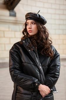 古い美しい通りで冬の秋のファッショントレンドの黒いフグコートと革の帽子ベレー帽でポーズをとるスタイリッシュな女性