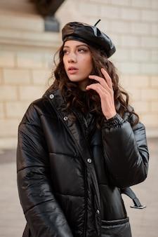 Стильная женщина позирует в зимней осенней модной тенденции черного пуховика и кожаной шляпы в берете на старой красивой улице