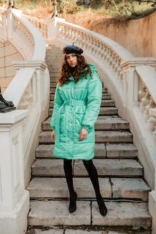 ハイヒールの靴を履いて古い美しい通りの階段で冬の秋のファッショントレンドの青いフグコートと帽子ベレー帽でポーズをとるスタイリッシュな女性