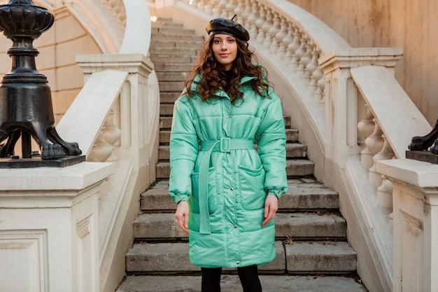 古い美しい通りの階段で冬の秋のファッショントレンドの青いフグコートと帽子ベレー帽でポーズをとるスタイリッシュな女性
