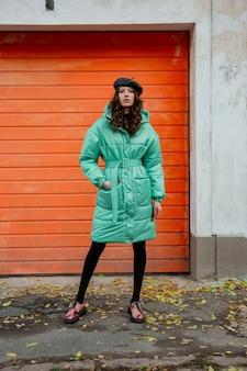 カラフルなプリントの靴を履いて通りのオレンジ色の壁に冬の秋のファッショントレンドフグコートと帽子ベレー帽でポーズをとるスタイリッシュな女性