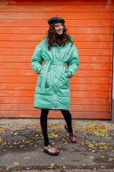 화려한 인쇄 신발을 입고 거리에 오렌지 벽에 겨울 가을 패션 트렌드 호흡기 코트와 모자 베레모 포즈 세련된 여자