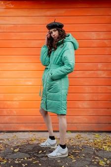 冬の秋のファッショントレンドのフグコートと帽子のベレー帽でポーズをとるスタイリッシュな女性は、スニーカーを身に着けている通りのオレンジ色の壁に