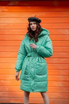 通りのオレンジ色の壁に冬の秋のファッショントレンドフグコートと帽子ベレー帽でポーズをとるスタイリッシュな女性