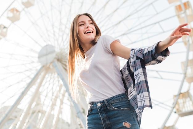 Woman posing near ferris wheel   Photo: Freepik