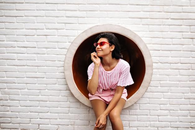 レンガの壁にポーズをとるスタイリッシュな女性。ピンクのサングラスでうれしそうな女性の屋外ショット。