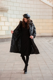 Stylish woman posing in winter autumn fashion trend black puffer coat and leather hat beret in old beautiful street wearing high heel shoes