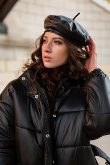 Elegante donna in posa in inverno autunno moda tendenza nero piumino e berretto in pelle cappello in vecchia bella strada