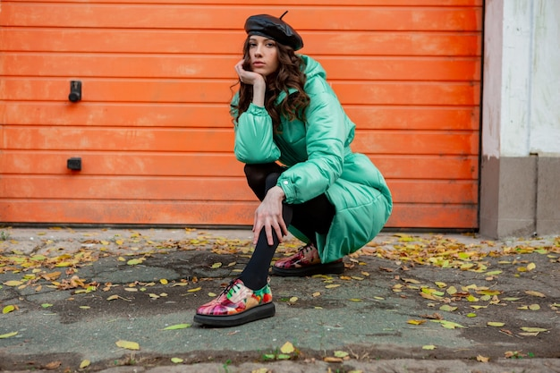 Stylish woman posing in winter autumn fashion trend puffer coat and hat beret against orange wall in street wearing colorful printed shoes
