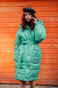 Stylish woman posing in winter autumn fashion trend puffer coat and hat beret against orange wall in street