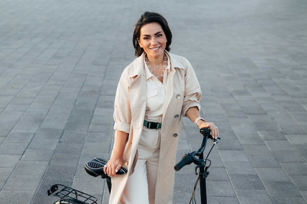 Stylish woman posing with bicycle outdoors