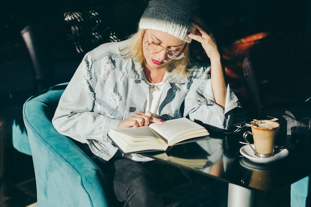 Stylish woman reading in cafe