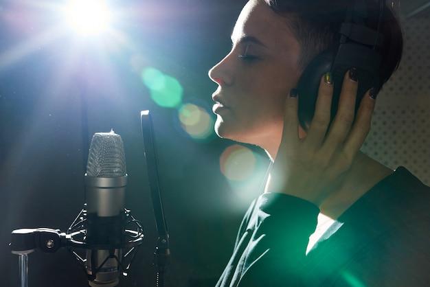 Stylish woman recording song in studio