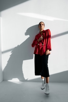 Stylish woman in red blazer and trousers fashionable autumn shoes suit classic portrait. high quality photo