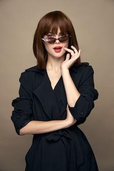 Стильная женщина сексуальный взгляд темные очки элегантный внешний вид бежевый фон