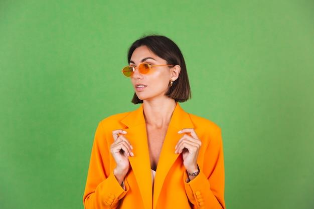 Stylish woman in silk beige dress and orange oversized blazer on green, positive emotions smile