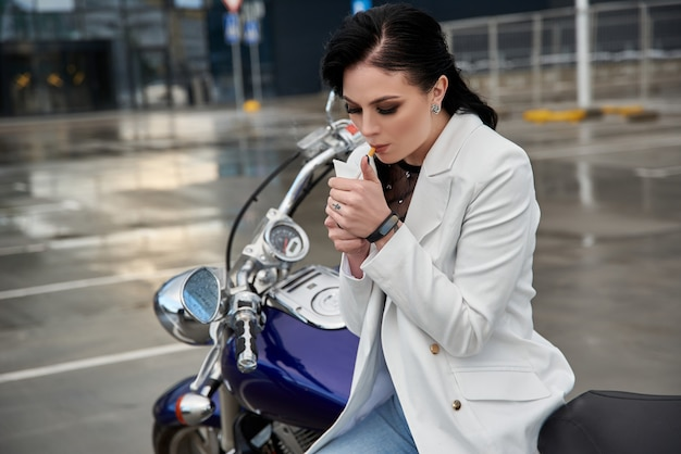 Stylish woman sits on a motorcycle and smokes a cigarette in the parking lot near the shopping center.
