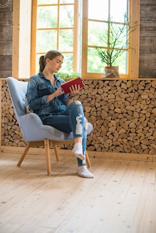 Stylish woman sitting on chair and reading book