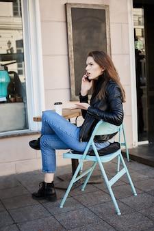 Стильная женщина сидит в патио кафе, пьет кофе и спорит во время разговора на смартфоне