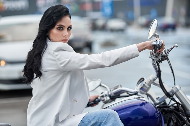 Stylish woman sitting on a motorcycle parked near a shopping center.