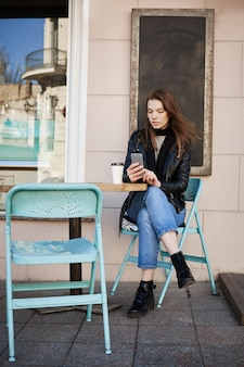 Stylish woman sitting in patio of restaurant, drinking coffee and making appointment to cosmetologist via internet, holding smartphone and typing