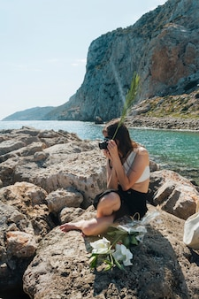 Stylish woman sitting on rock holding palm leaves while taking photo with camera