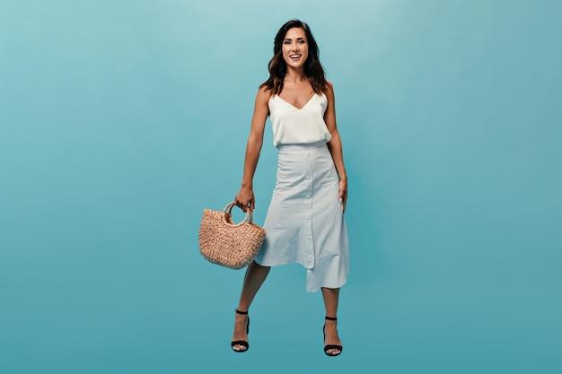 Elegante donna in gonna e top tiene borsa di paglia su sfondo blu