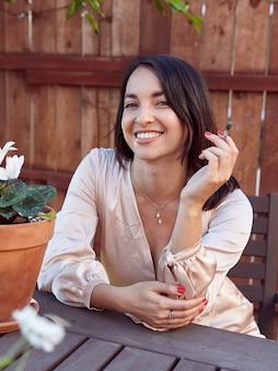 Donna alla moda che fuma una canna all'esterno