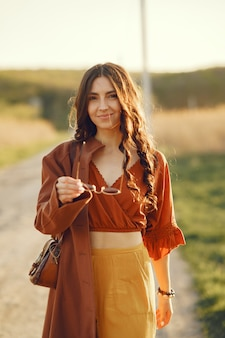Stylish woman spending time in a summer field