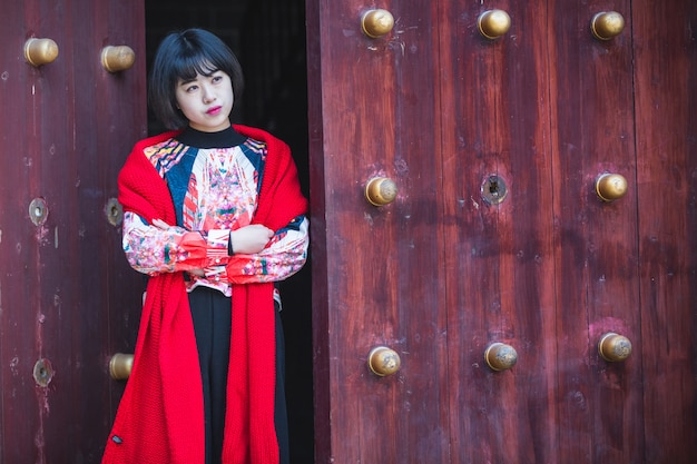 スタイリッシュな女性は、伝統的な木製のドア Premium写真