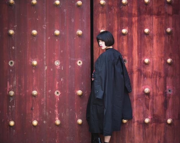 スタイリッシュな女性は、伝統的な木製のドア