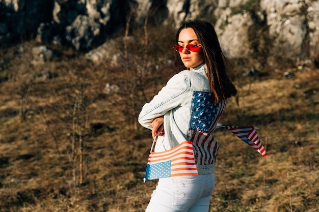 Stylish woman standing on nature with flags of united states