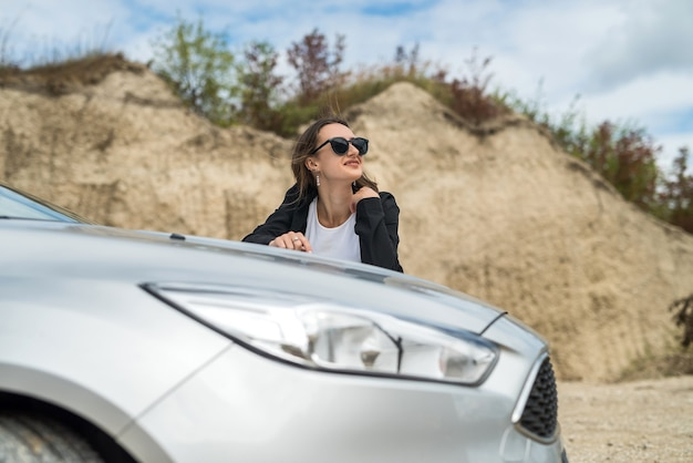 Stylish woman standing near her car and enjoy freedom in nature outside city, summer time