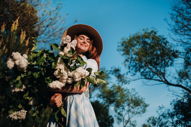 A stylish woman in a straw hat and a straw bag poses with a bouquet of white lilac in a sunny spring park.