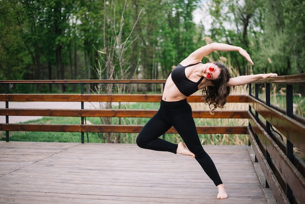 Stylish woman stretching muscles with holding railing