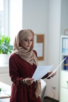 スタイリッシュな女性。テーブルの近くに立って、ドキュメントを読んでヒジャーブを身に着けているスタイリッシュなイスラム教徒の女性