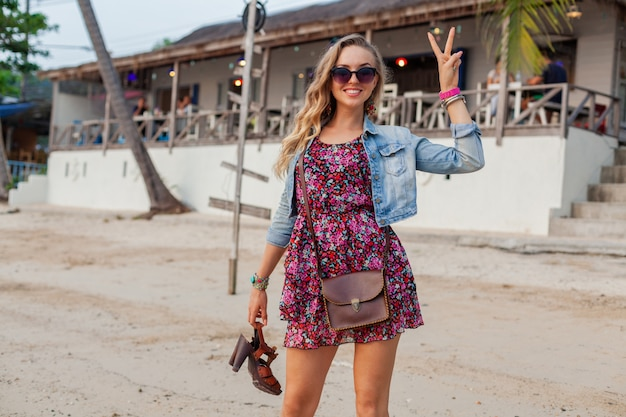 Stylish woman in summer dress vacation walking on beach with shoes in hand