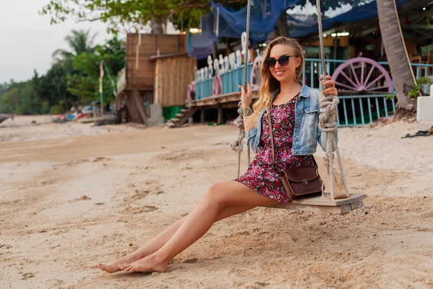 Stylish woman in summer dress vacation walking on beach with sunglasses