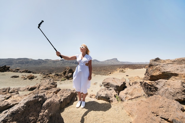A stylish woman takes a selfie in the crater of the teide volcano.
