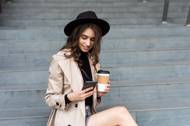 電話で話し、屋外でコーヒーを飲むスタイリッシュな女性。屋外でビジネスウーマン。
