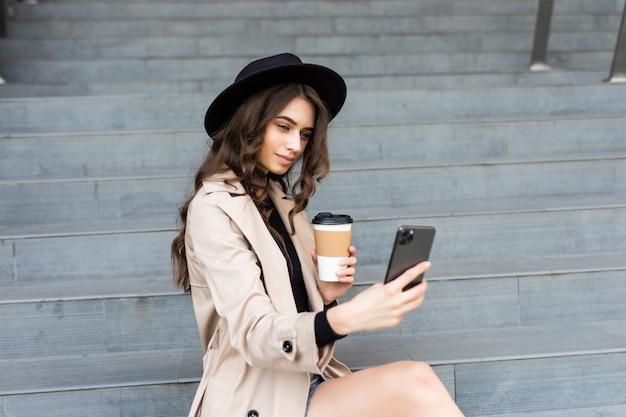 전화 통화 하 고 야외에서 커피를 마시는 세련 된 여자. 비즈니스 여자 야외.