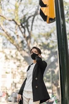 医療マスクを着用しながら屋外で電話で話しているスタイリッシュな女性