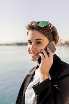 Стильная женщина разговаривает по телефону на открытом воздухе