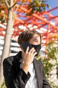 Donna alla moda che parla al telefono mentre indossa una mascherina medica