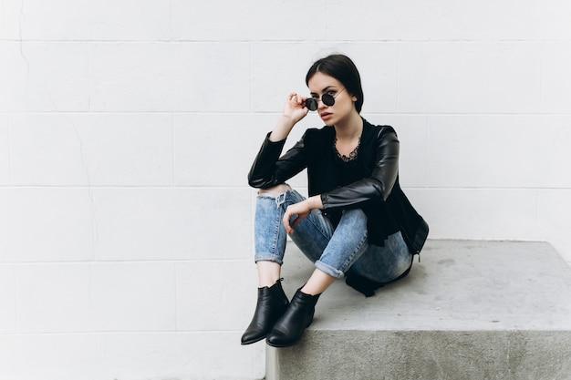 Стильная женщина, касаясь солнцезащитных очков